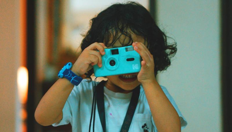 Ein Kind schaut durch eine kleine blaue Kamera.