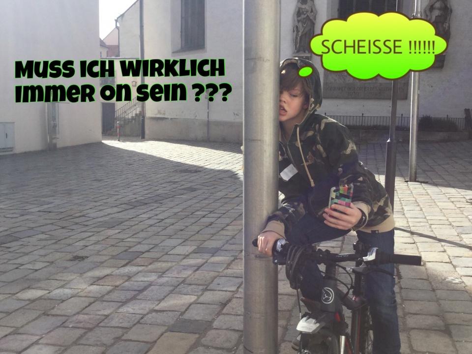 Überschrift: Muss ich wirklich immer online sein? Ein Jungen auf einem Fahrrad ist gegen einen Laternenpfahl gefahren, da er von der Bedienung seines Smartphones abgelenkt war. Über seinem Kopf befindet sich eine Gedankenblase. Er denkt: Scheiße!