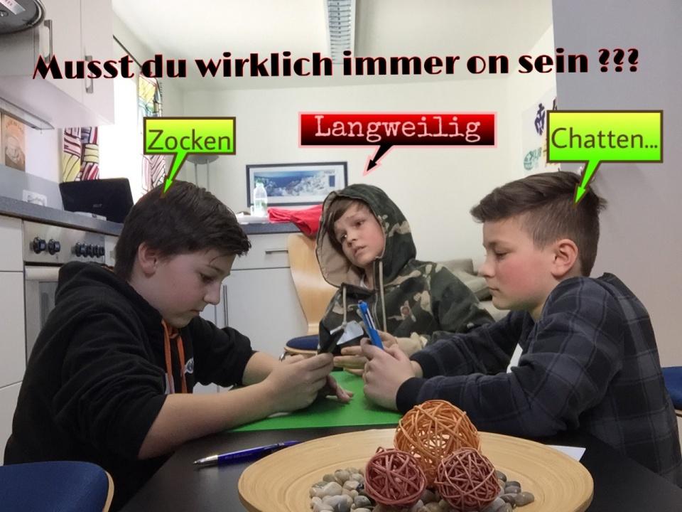 Überschrift: Musst du wirklich immer on sein?  Drei Jungen sitzen gemeinsam an einem Küchentisch. Zwei der Jungen beschäftigen sich mit ihren Smartphones. Einer der beiden spielt ein Handyspiel, der andere chattet. Der dritte Junge langweilt sich währenddessen und sieht unglücklich aus.