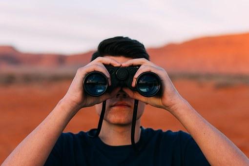 Ein Mensch blickt durch ein Fernglas in die Ferne. Im Hintergrund befinden sich rote Sandberge.