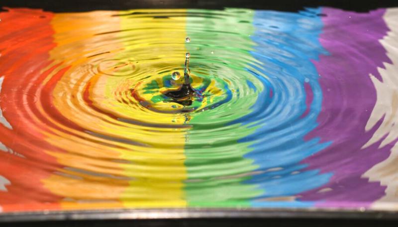 Ein Wassertropfen tropft in eine Wasserpfütze, in der sich eine Regenbogenflagge spiegelt.