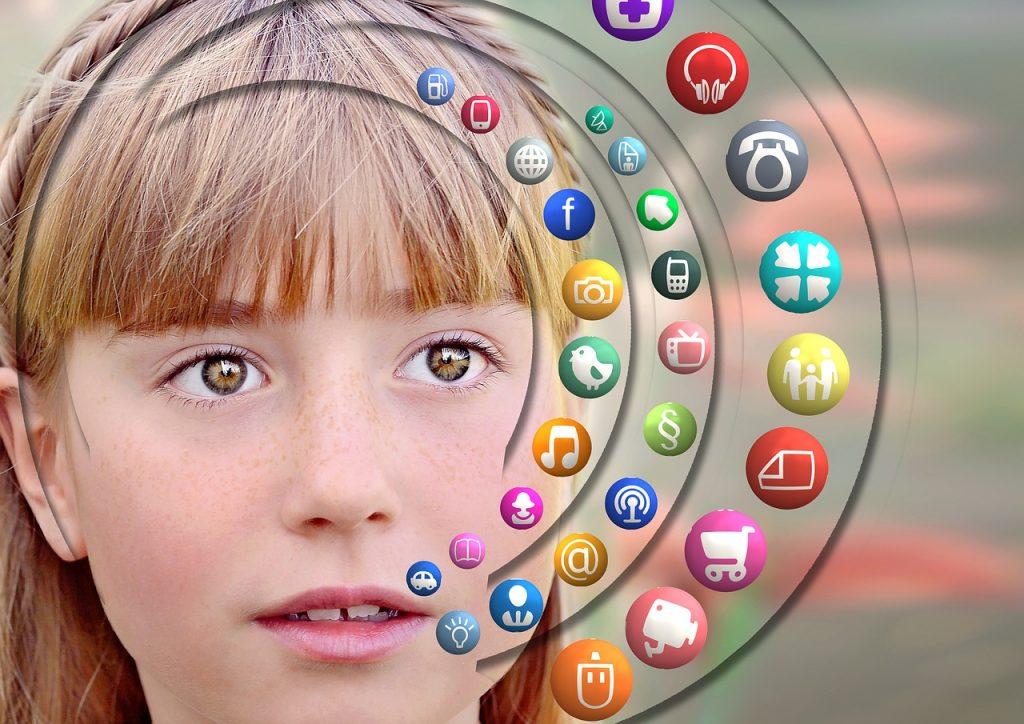 Das Gesicht eines Mädchen, das interessiert in die Kamera blickt. Auf der rechten Seite befinden sich viele kleine, bunte Icons mit verschiedenen Symbolen, wie z.B. einem Auto, einer Kamera, einem Einkaufswagen oder dem @-Zeichen.