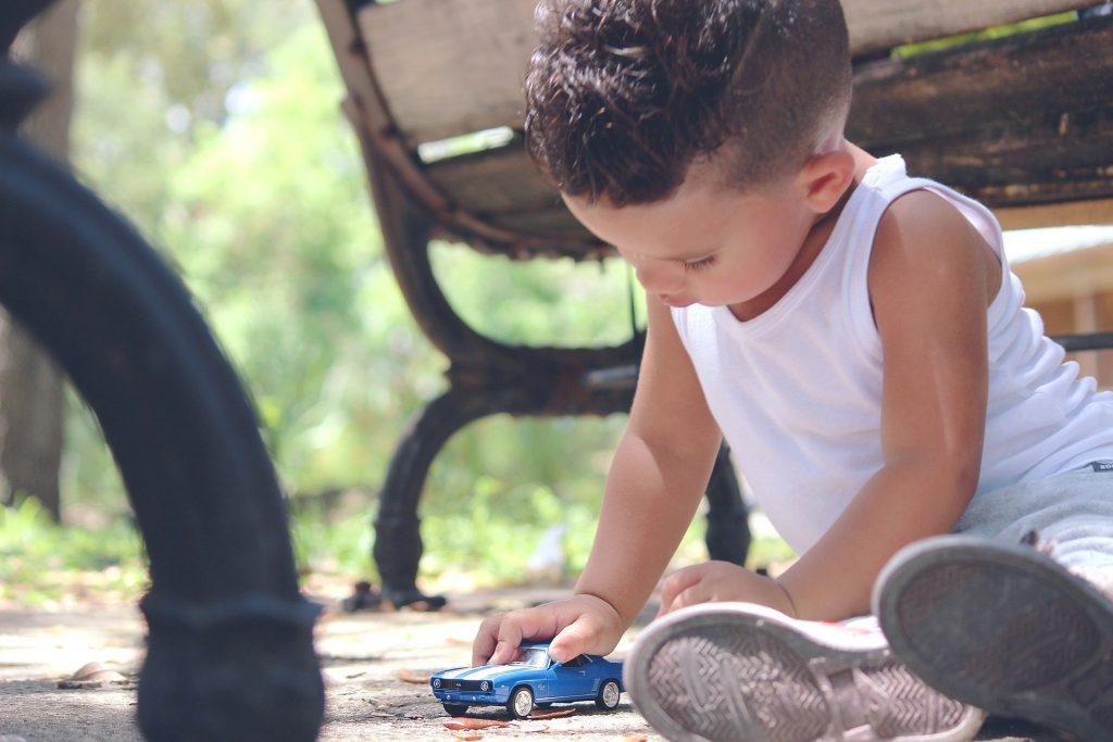 Ein Kleinkind spielt mit einem blauen Spielzeugauto auf dem Boden.