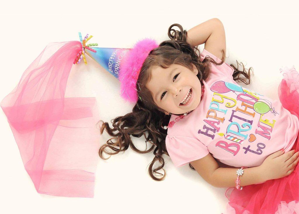 Ein Kind liegt lächelnd auf dem Boden. Es hat lange lockige Haare, trägt pinke Kleidung und einen Party-Hut auf dem Happy Birthday steht. Es sieht glücklich aus.