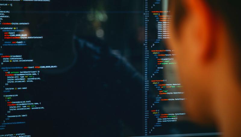 Ein Mensch blickt auf einen Code auf dem Computerbildschirm.
