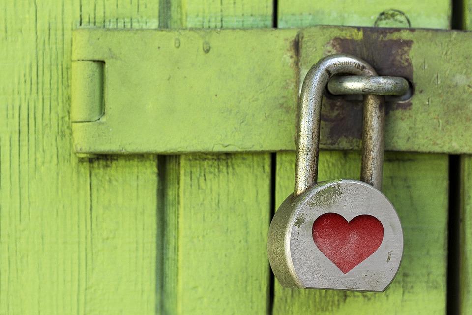 Eine verschlossene Holztür. Sie ist mit einem Vorhängeschloss, das mit einem Herz verziert ist, gesichert.