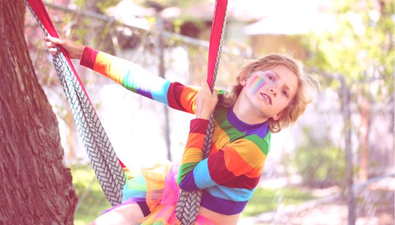 Ein Kind im Regenbogenpulli schaukelt auf einer Hängematte.