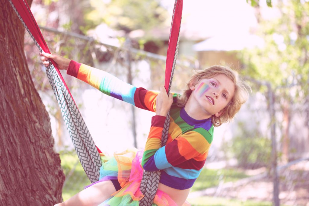 Ein Kind schaukelt, bunt gekleidet, und mit einer geschminkten Regenbogenfahne im Gesicht auf einer Hängematte, die an einem großen Baum hängt.