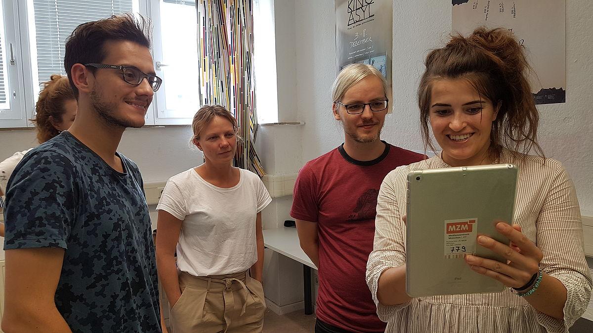 Vier Teilnehmende eines Blended Learning-Kurses zur geschlechtsbezogenen Medienpädagogik betrachten ein Tablet.