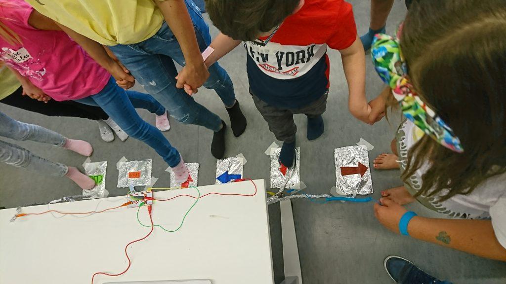 Kinder halten sich an den Händen und spielen zusammen ein Spiel