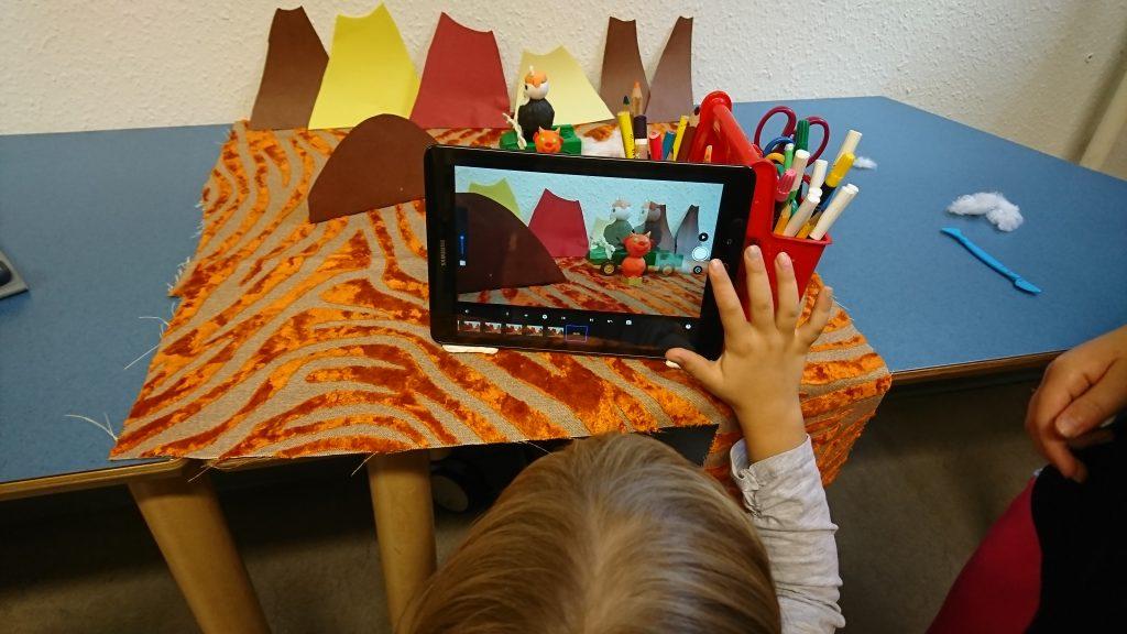 Ein Kind nimmt ein Video eines gebastelten Stilllebens auf