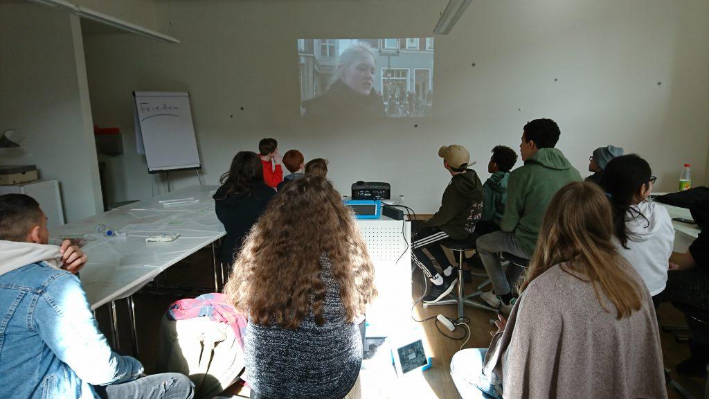 Jugendliche sehen gemeinsam einen Film, der auf die Wand projiziert wird.