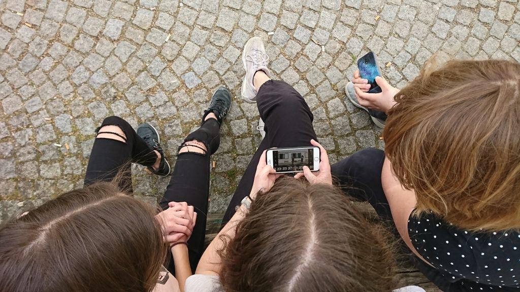 Drei Kinder sitzen nebeneinander und blicken auf ein Kameradisplay