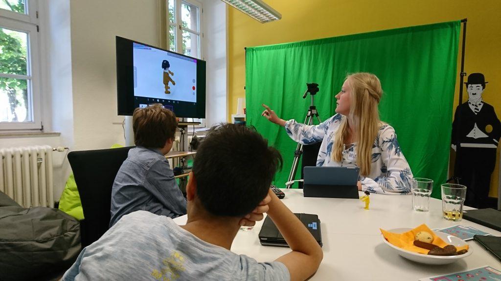 Eine Person sitzt gemeinsam mit zwei Kindern an einem Tisch und deutet auf einen Fernseher. Sie erklärt etwas zum Thema Filmaufnahmen.
