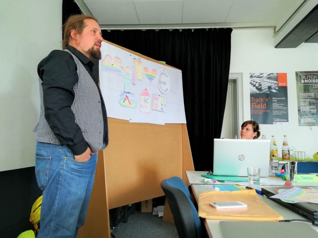 Markus Nau. Er steht neben der Collage und referiert.