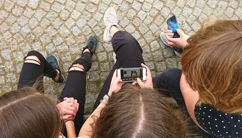 Drei Jugendliche schauen sich gemeinsam ein Bild auf einem Smartphone an.