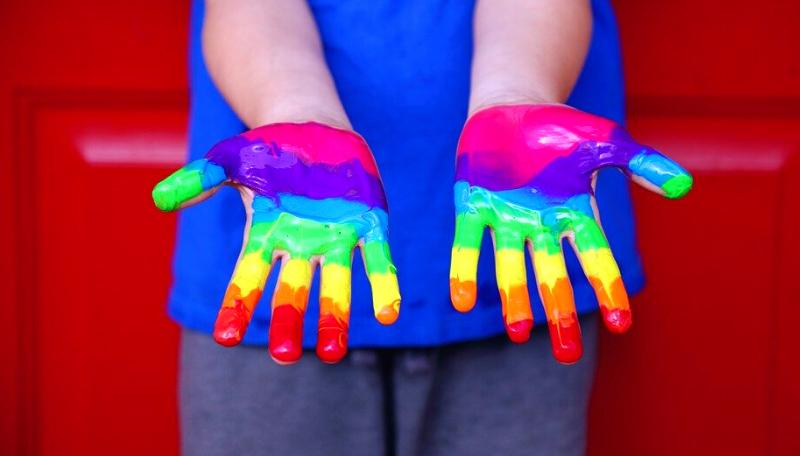 Ein Kind hält seine bunt in Regenbogenfarben bemalten Hände in die Kamera.