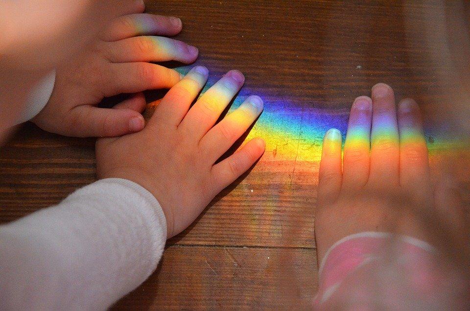 Foto: Kinderhände die versuchen einen Regenbogen, der durch Brechung des Lichts auf einem Holzboden entstanden ist, zu greifen.