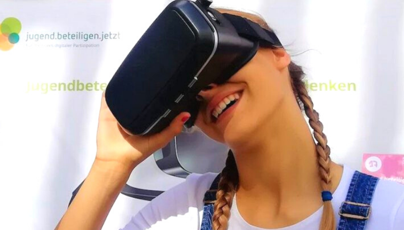 Person lächelt in die Kamera und trägt eine Virtual Reality Brille.