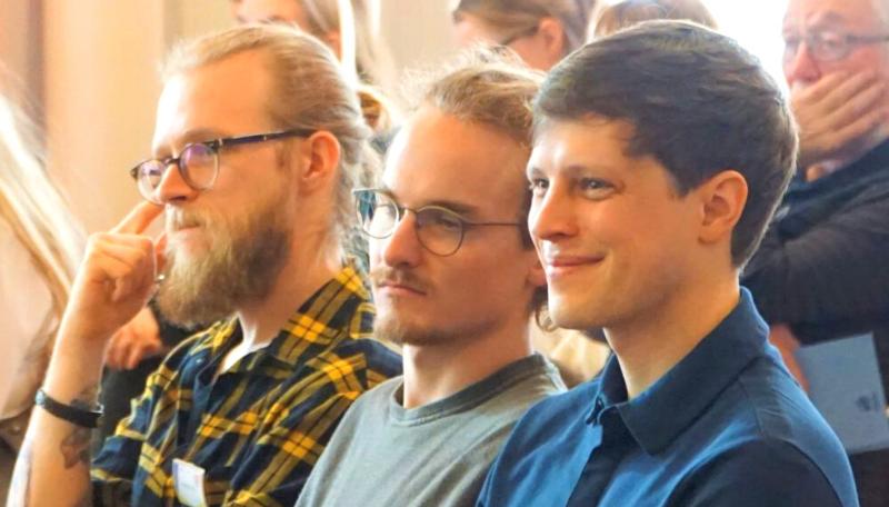 Fabian Wörz und Linus Einsiedler sitzen seitlich und lächeln.