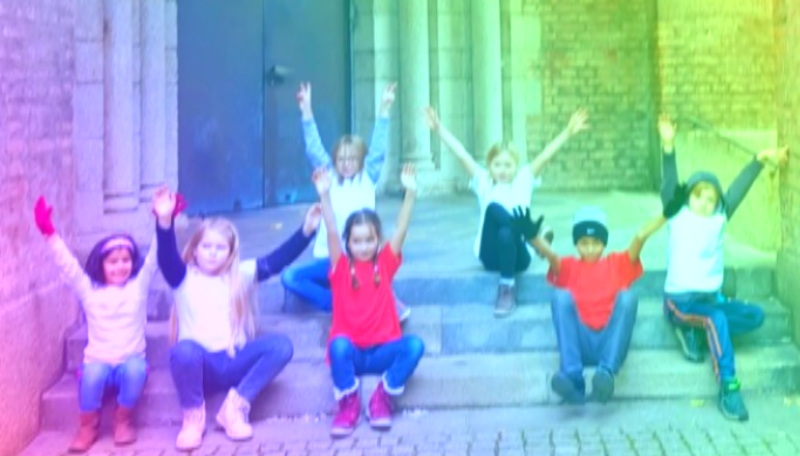 Sieben Kinder sitzen auf einer Treppe und strecken ihre Arme nach oben in die Luft.