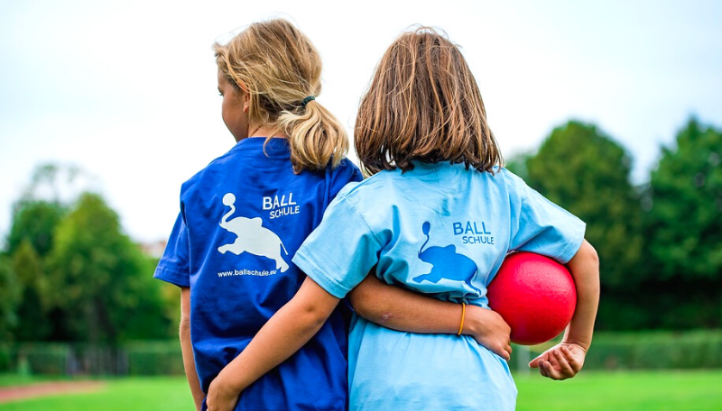 Zwei Kinder haben sich gegenseitig die Arme um die Hüfen gelegt. Das eine Mädchen trägt in ihrem rechten Arm einen roten Ball.