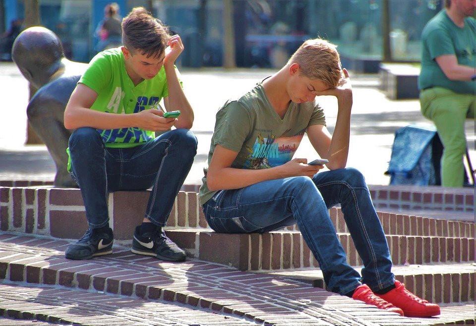 Zwei Jugendliche sitzen auf einer Treppe und schauen auf ihre Smartphones.