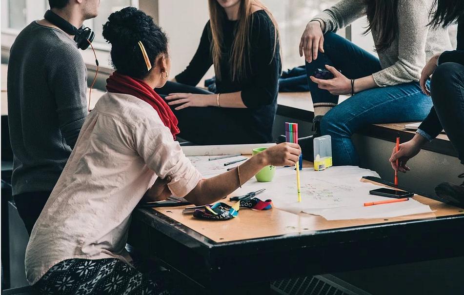 Jugendliche einer Schulklasse sitzen gemeinsam um einen Tisch und unterhalten sich