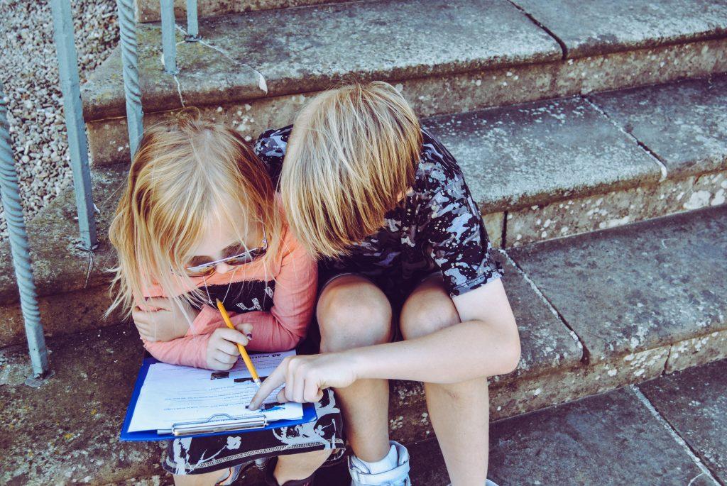 Zwei Kinder sitzen auf eine Treppe und füllen zusammen ein Quiz aus