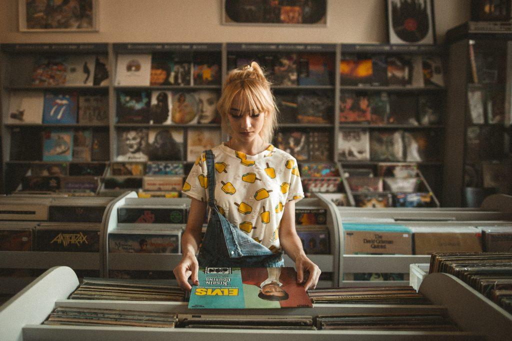 Eine Person steht in einem Plattenladen und sieht sich eine Schallplatte an.