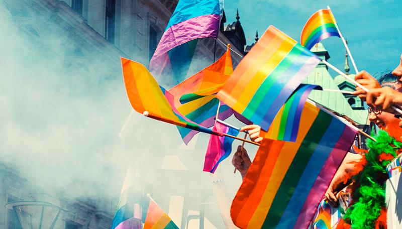 Mehrere Regenbogenflaggen wehen im Wind.