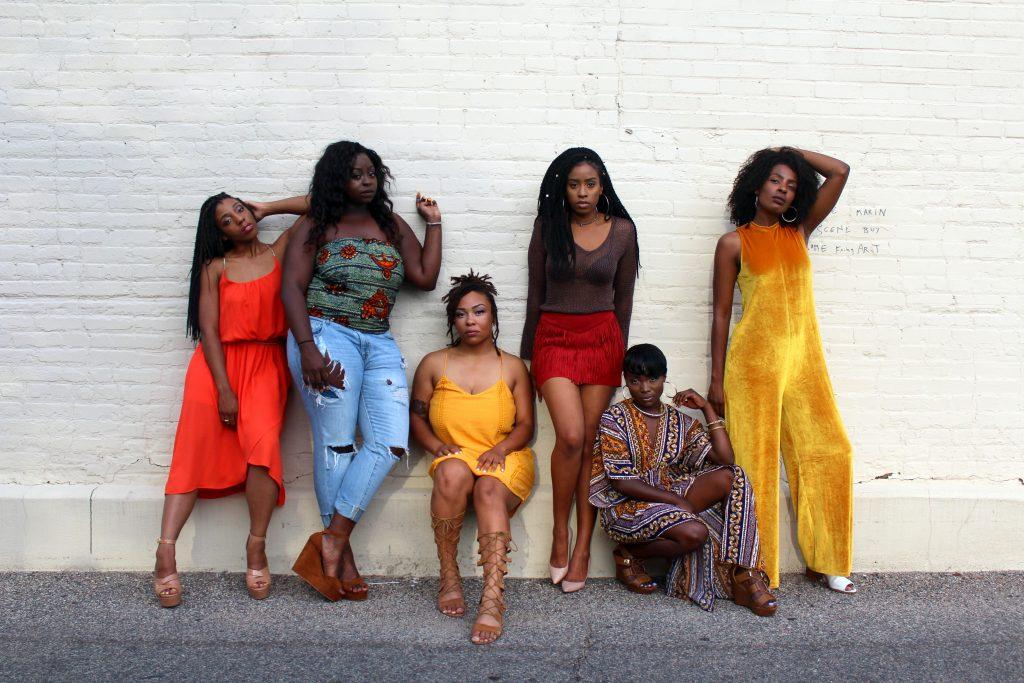 Sechs Schwarze Jugendliche posieren in einer Reihe, bunt gekleidet, auf der Straße an eine weiße Wand gelehnt.