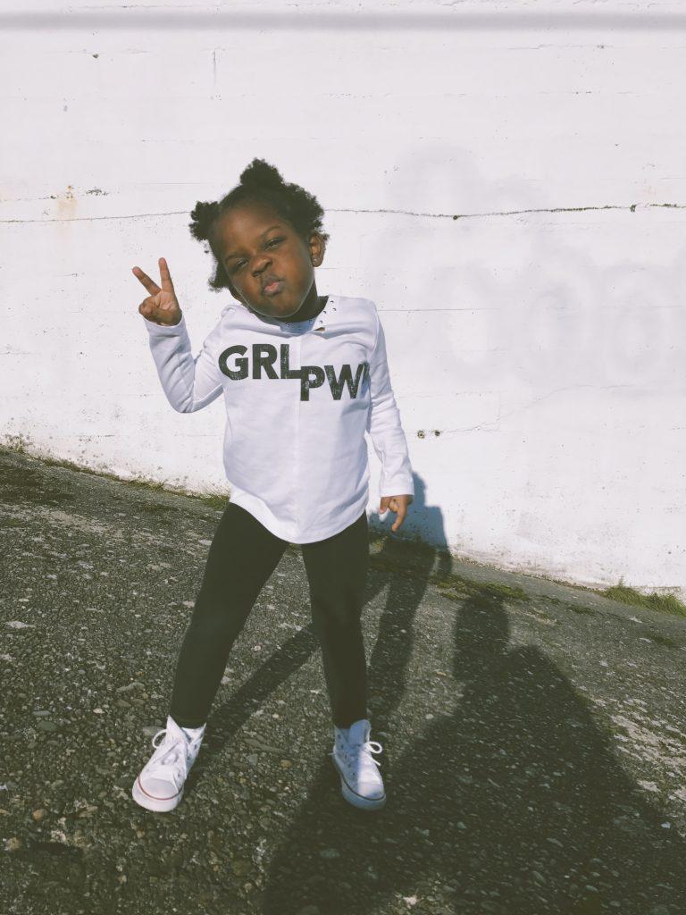Ein Kind formt mit der Hand das Peace-Zeichen. Auf dem Pullover steht GirlPower