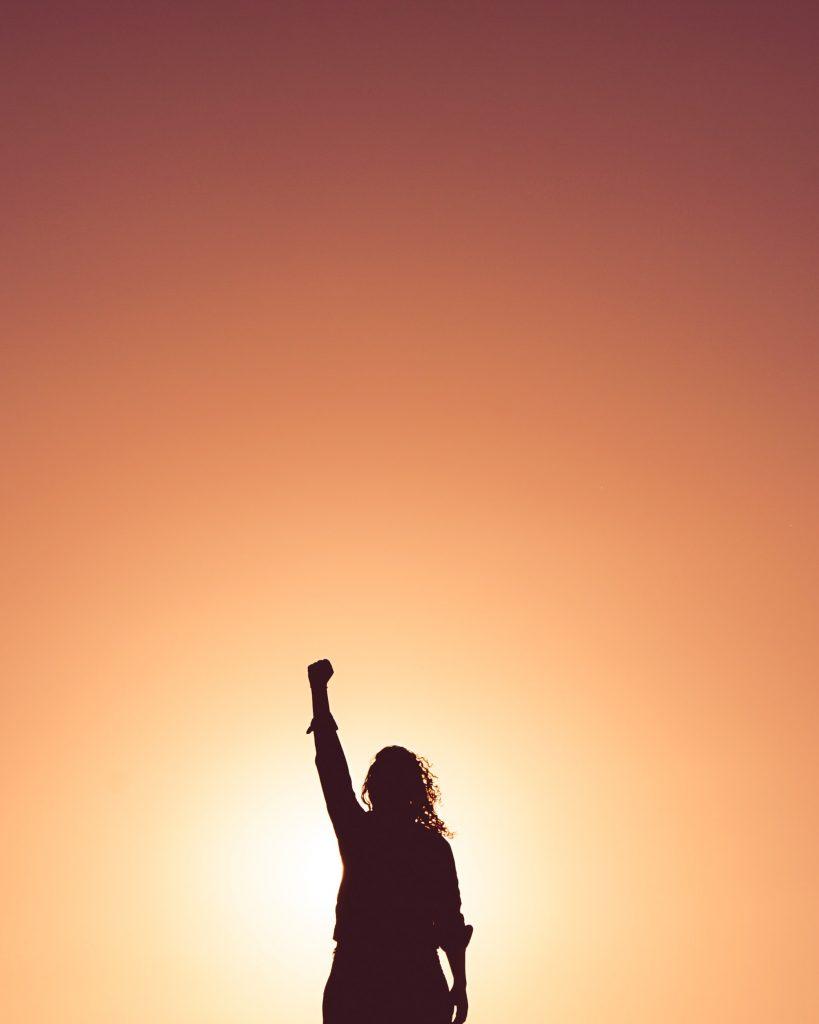 Ein Mensch streckt den Arm und die Hand kraftvoll nach oben