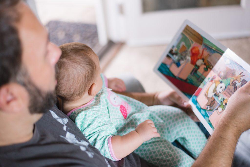 Ein Baby liegt auf dem Schoß eines Mannes, der ein Bilderbuch in der Hand hält.