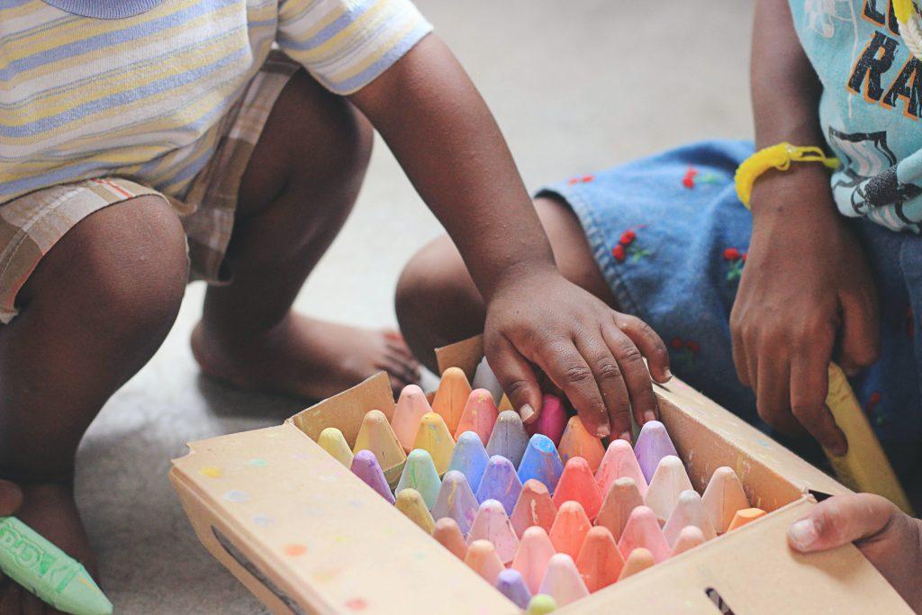 Zwei Kinder knien vor einer Kiste mit Straßenmalkreiden.