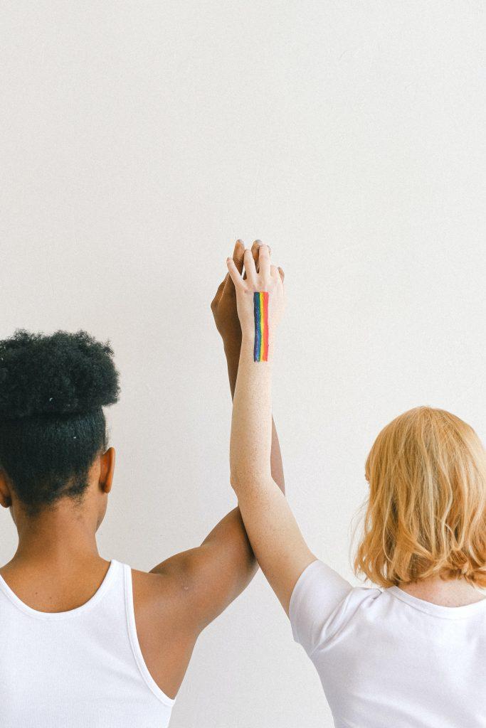 Zwei Menschen stehen, mit dem Rücken zur Kamera, nebeneinander. Eine Person ist dunkelhäutig, die andere hellhäutig. Gemeinsam halten sie sich an der Hand und strecken diese nach oben in die Luft.  Dabei sieht man eine gezeichnete Regenbogenflagge, die sich auf dem Arm der rechten Person befindet.