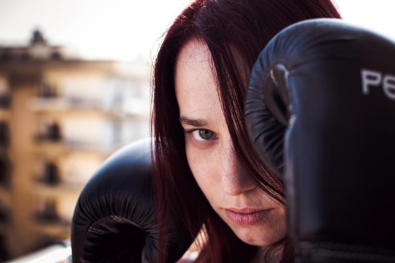 Ein*e Jugendliche*r trägt Boxhandschuhe und blickt mit erhobenen Fäusten, entschlossen in die Kamera.