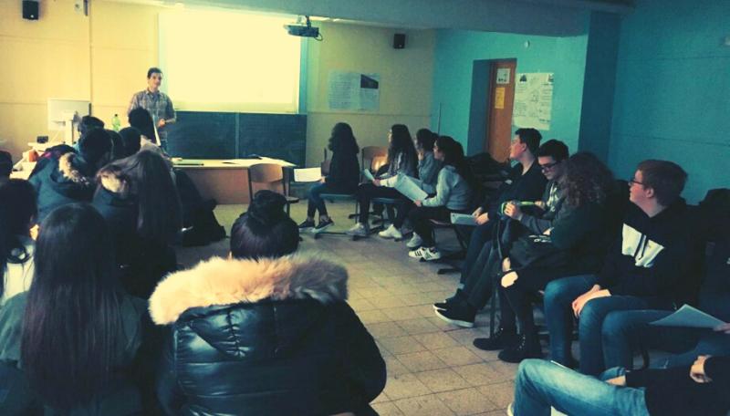 Eine Gruppe von Menschen sitzt im Kreis und schaut an die Tafel.
