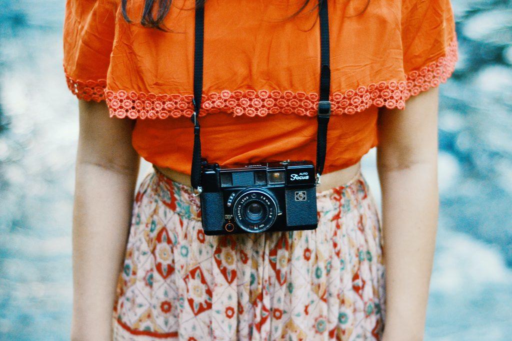 Mädchen trägt eine Kamera um ihren Hals.