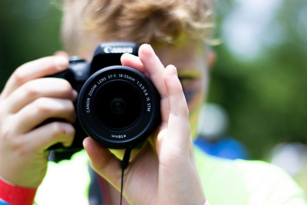 Junge blickt durch eine Spiegelreflexkamera.