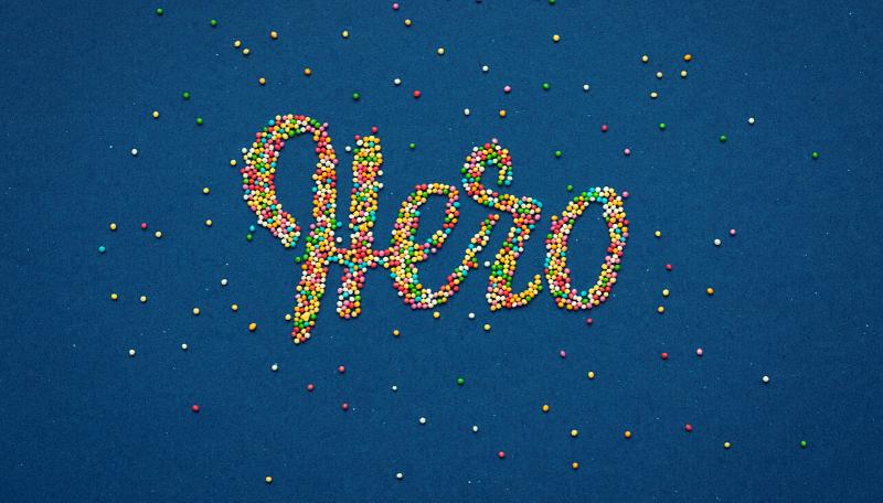 Aus kleinen bunten Kugeln wurde auf blauem Hintergrud das Wort: Hero gelegt.