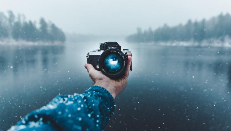 Vor einem See wird eine Kamera in der Hand gehalten.