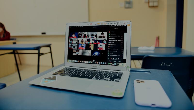 Auf einem Tisch steht ein Laptop, auf dem ein Online-Video-Tool geöffnet ist.