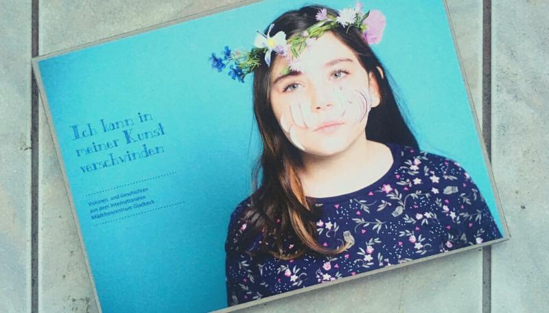 Blaues Buch auf dem ein Mädchen* mit Blumenkranz abgebildet ist.