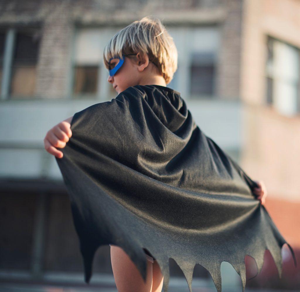 Ein Kind mit einem Superheld*innen-Kostüm