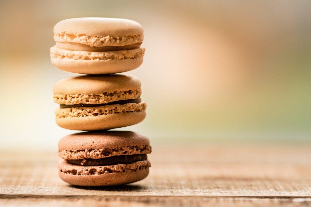 Drei braune Macarons die aufeinander gestappelt sind.