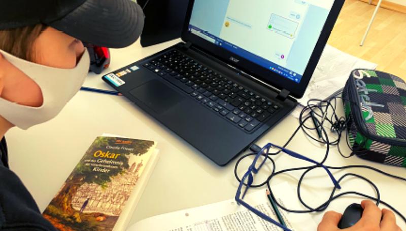 Ein Junge trägt eine Mund-Nasen-Bedeckung und arbeitet am Laptop.