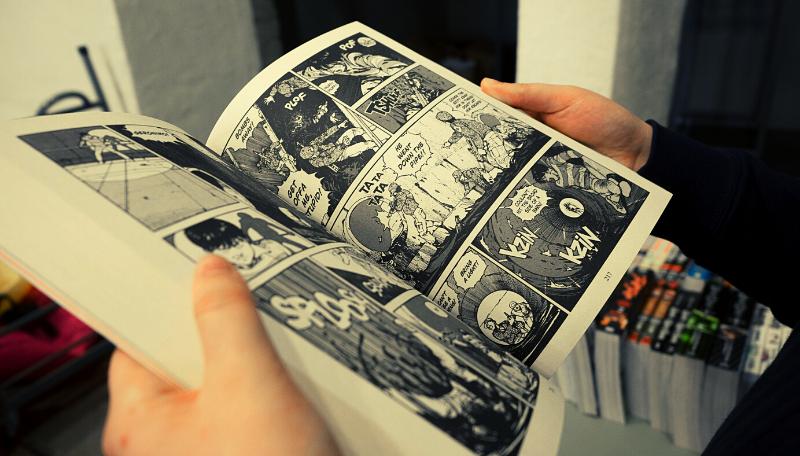 Zwei Hände halten ein Comic in der Hand.