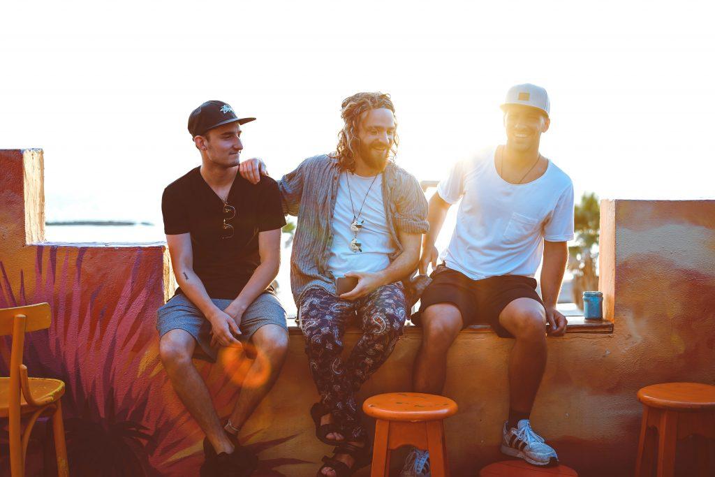 Drei Jugendliche sitzen bei Sonnenschein zusammen in einer Bar.